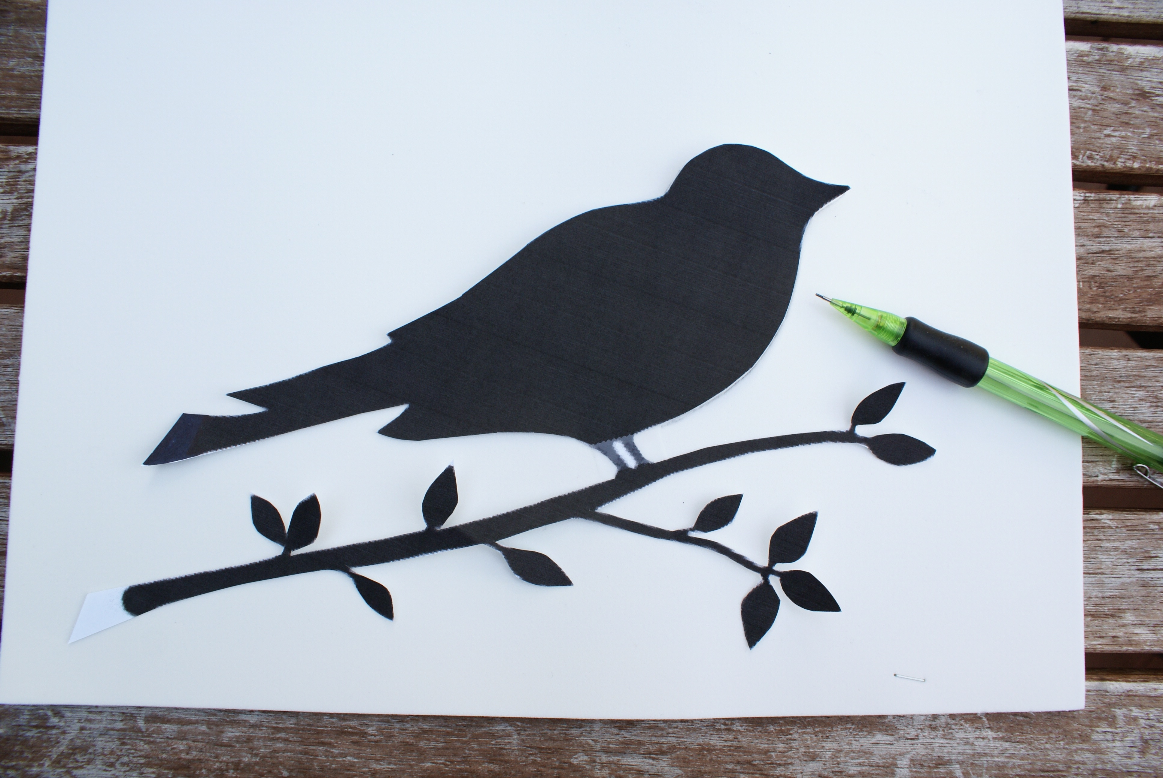 Preparing to trace bird on branch from cutout stencil onto foam